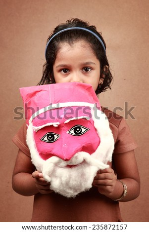 Little Indian girl holds a mask of Santa - stock photo