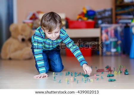 Little joyful blond child playing with lots of small toy soldiers, indoor. Active kid boy with glasses wearing colorful shirt and having fun at home or at nursery. - stock photo