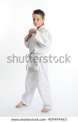 Little karate boy posing clenches his fists - stock photo