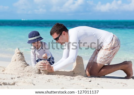 little kid and his father building sandcastle - stock photo