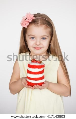 Little kid blonde girl holding a red velvet cake isolated on white background. Birthday concept - stock photo