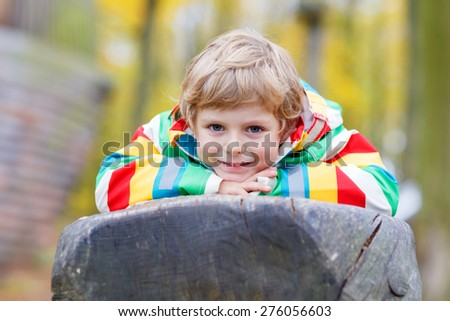 Little kid boy in colorful rain jacket with stripes  having fun with playing on playground on warm, autumn day, outdoors - stock photo
