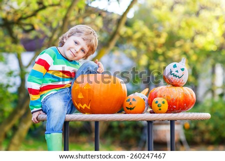 Little kid boy posing with traditional jack-o-lantern for halloween in autumn garden, outdoors. Child having fun on sunny warm october day. Creative and active leisure - stock photo