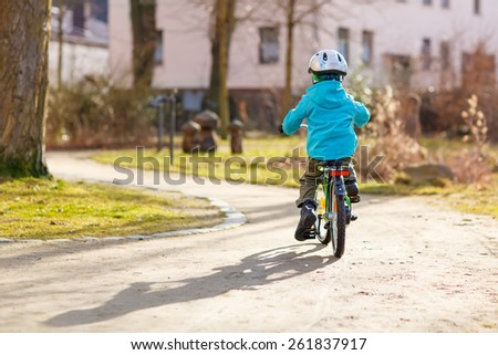 Little kid boy riding with his first green bike in the city park. Happy child in colorful clothes. Active leisure for kids outdoors. - stock photo