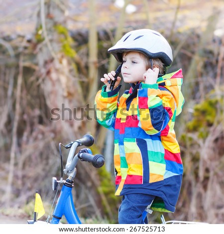 Little kid boy wearing safety helmet and riding his first bike and having fun on cold  day, outdoors. Active leisure with children in winter, spring or autumn. - stock photo