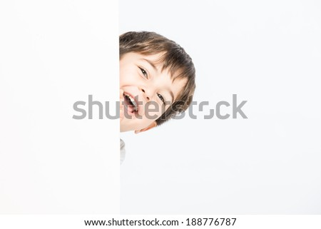 Little kid enjoying posing while playing hide and seek - stock photo