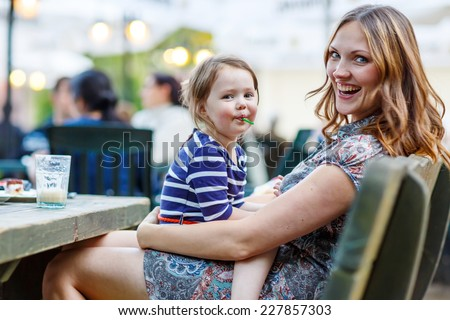 Little kid girl and her beautiful mother relaxing together with her little daughter, adorable toddler girl, in summer outdoors cafe drinking coffee on warm summer evening - stock photo