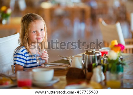 Little kid having breakfast at outdoor cafe. Adorable girl drinking fresh watermelon juice enjoying breakfast. - stock photo