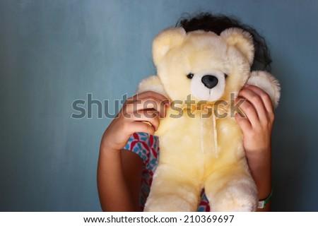 little kid hiding behind teddy bear. selective focus. - stock photo