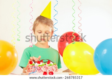 Little kid in festive hat looking at the birthday cake - stock photo