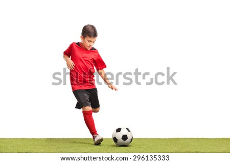 Little kid in red football jersey kicking a football on a grass surface isolated on white background - stock photo