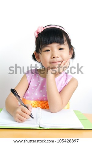 Little kid is doing her home work with smiling face - stock photo