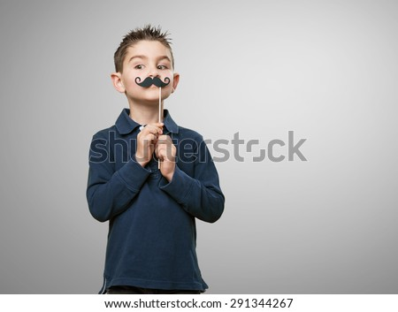 little kid joking with a moustache - stock photo