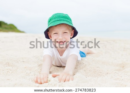 little kid laying at the sand and enjoying day at the beach at taketomi island, okinawa, japan - stock photo
