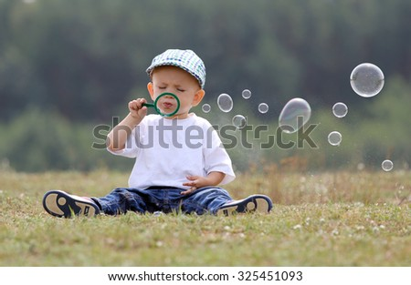 Little kid making soap bubbles in the park - stock photo