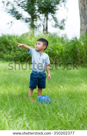 Little kid play soccer ball and finger point aside - stock photo