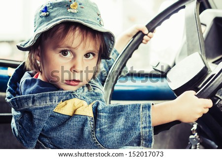 Little kid playing at the wheel of car - stock photo