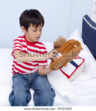 Little kid playing baseball in his bedroom - stock photo