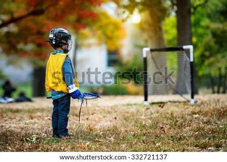 Little kid playing lacrosse with his stick in the autumn park - stock photo