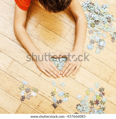 little kid playing with puzzles on wooden floor together parent, lifestyle people concept, loving hands to each other - stock photo
