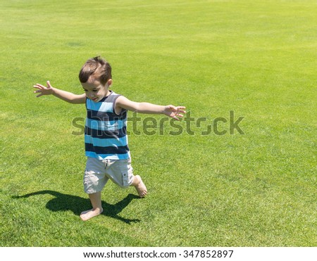 Little kid running on green meadow - stock photo