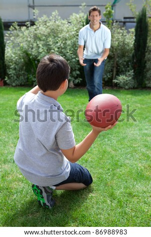 Little kid throwing football to his father in backyard - stock photo