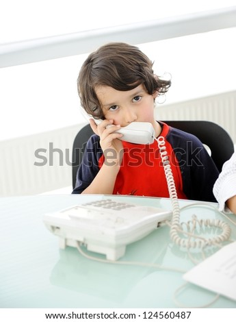 Little kid using phone in business office - stock photo