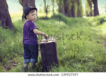 Little kid with big suitcase - stock photo