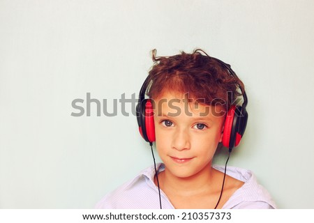 little kid with headphones  listening to music . room for text. - stock photo