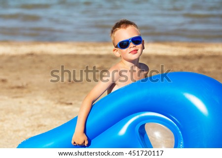 Little kid with inflatable mattress on the beach. Smiling boy playing on the beach with air mattress. Child is going to swim in the sea with swimming mattress. Summer vacation - stock photo