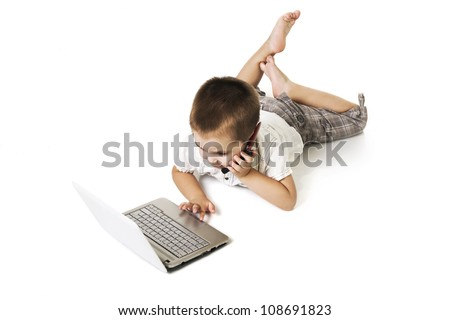 little kid with laptop talking on mobile phone - stock photo