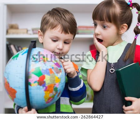 Little kids are examining globe in the classroom - stock photo