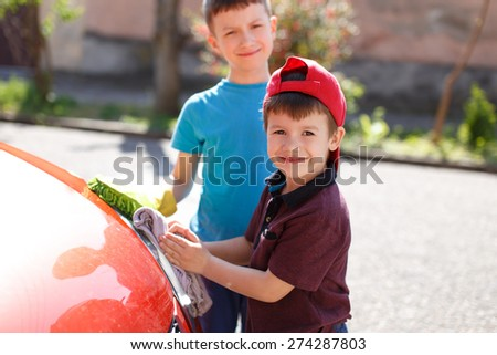 Little kids cleaning red car headlight, outdoor portrait - stock photo