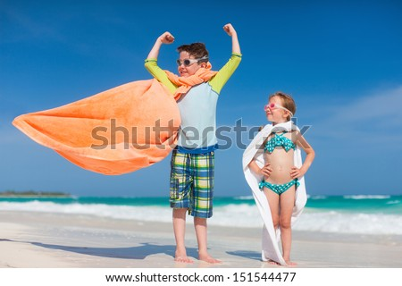 Little kids playing superheroes at a tropical beach - stock photo
