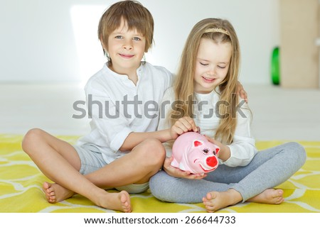 Little kids with piggy bank - stock photo