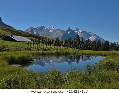 Little Lake And Mountain Range In The Saanenland - stock photo