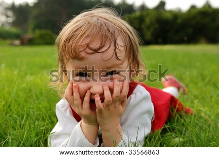 Little laughing girl closing her mouth with hands lying on green grass in the garden summertime - stock photo