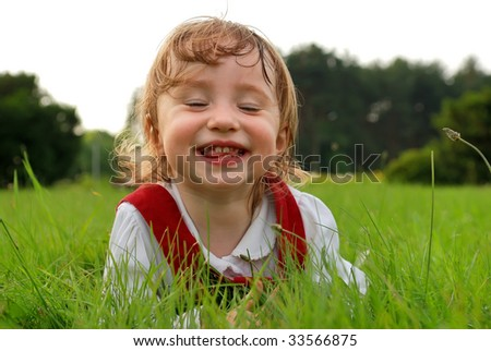 Little laughing girl with closed eyes lying on green grass in the garden summertime. See my other photos from this series - stock photo