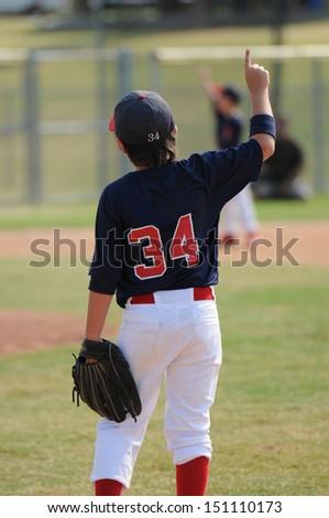 Little league baseball boy calling one out. - stock photo
