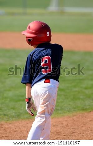 Little league baseball boy standing on base with helmet - stock photo