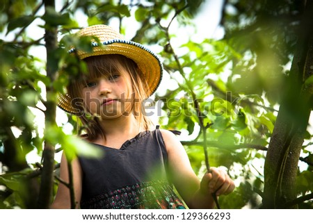 Little lovely beautiful girl posing in a straw hat in the park. - stock photo