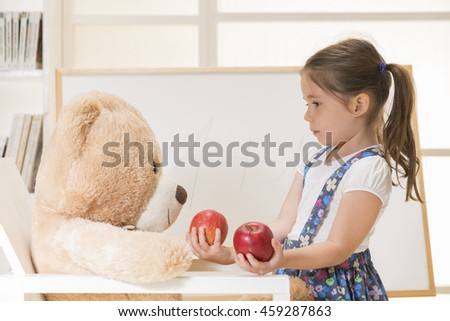 Little lovely caucasian child sharing apples with her Teddy bear friend. Little girl teaching her toy bear friend to count with apples, indoor shot. Cute toddler playing teacher role game. - stock photo