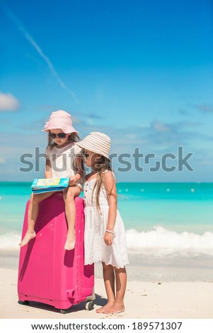Little lovely girls with big suitcase and a map searching for the way on tropical beach - stock photo