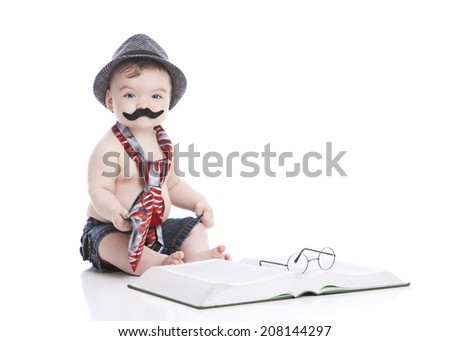 Little man.  Adorable little boy wearing a neck-tie, hat, and handle bar mustache next to a large book with glasses on top.  Isolated on white with room for your text. - stock photo