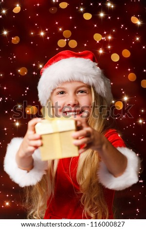 little miss santa shaking a gift to find out what is inside - stock photo
