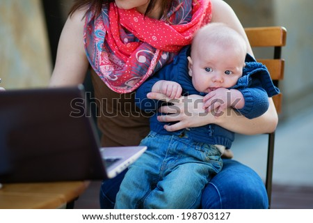 Little 4-month baby in his mother's arms while she's working on her laptop - stock photo