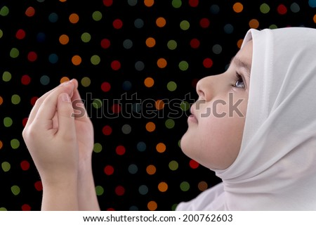 Little Muslim Girl Prayer on Defocused Night Lights Background - stock photo