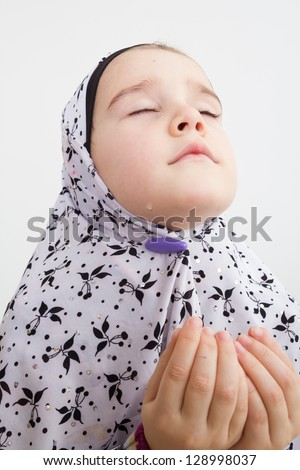 Little muslim girl praying holding her hands up - stock photo