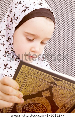 Little Muslim girl with the holy Quran. - stock photo