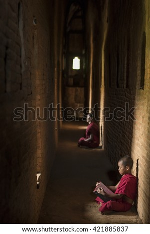 Little Myanmar monk reading book, sitting in monastery, Bagan, Myanmar - stock photo